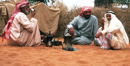 Men drinking karak out of traditional Emirati teapots