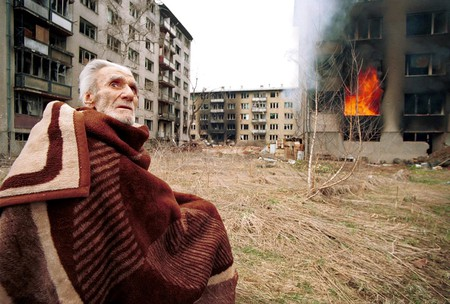 A Bosnian Croat man sits stunned and scared outside his burning home after rampaging Bosnian Serbs looted and set fire to his home in the final hours of siege on Mar 17, 1996 in Sarajevo, Bosnia | © Northfoto/Shutterstock