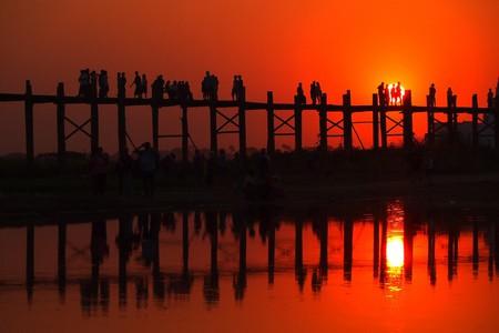 The sun sets vibrantly at U Bein Bridge near Amarapura, Myanmar   © momo / Flickr