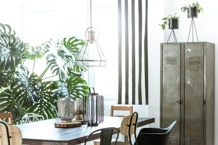White, industrial dining room with metal wardrobe and wood table | @ Photographee.eu/Shutterstock