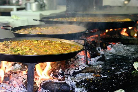 Valencian paella cooking over a wood fire.
