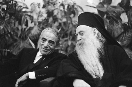 Onassis (left) talks with Patriarch Athenagoras in the VIP room at Schiphol