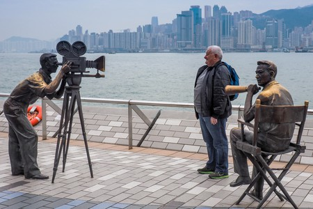 A tourist posing for a photograph on the Avenue of the Stars, Kowloon, Hong Kong