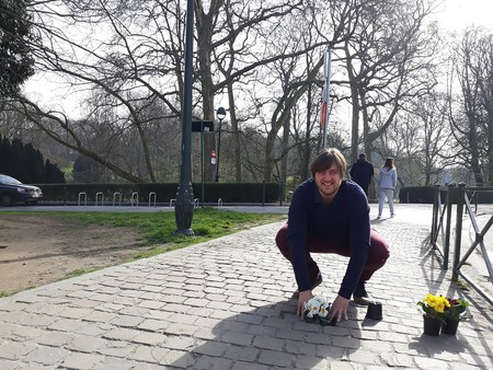 Guerrilla gardener Anton Schuurmans planting flowers in a pothole on a city road in Brussels