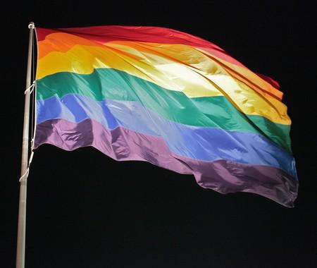 A rainbow Pride flag set against a night sky