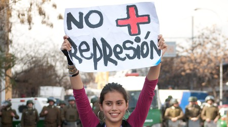 A protestor holding a NO + sign during a previous protest