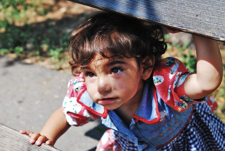 A Roma girl is playing and hiding on a wooden bench, Belgrade, Serbia.