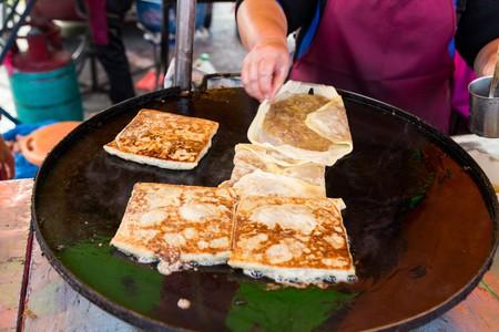 Vendor preparing traditional murtabak cuisine at street bazaar in Malaysia