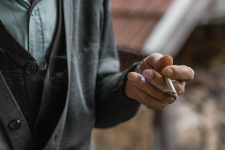 Elderly man holding a cigarette