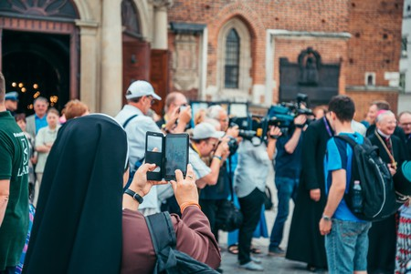 A nun filming on a mobile phone