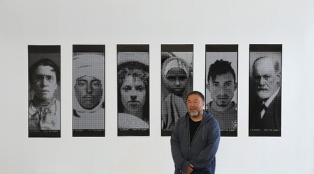 Artist Ai Weiwei stands in front of artworks 'Banner 51,' 'Banner 2,' 'Banner 13,' 'Banner 200,' 'Banner 90,' and 'Banner 50'