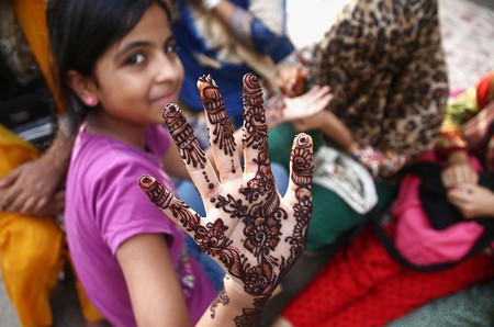 A Pakistani girl shows the henna tattoo on her hand, ahead of Eid al-Fitr