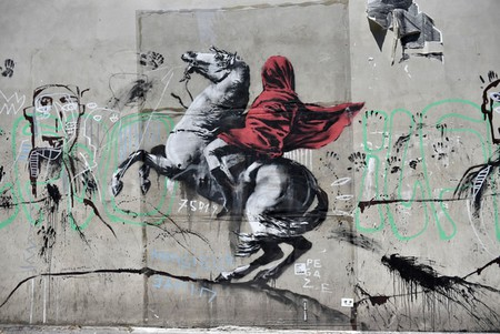 People walk by a recent artwork believed to be attributed to Banksy showing Napoleon rearing his horse, wrapped in a red cloak in the 19th district of Paris, France, June 26, 2018. Several artworks attributed to the anonymous British street artist appeared in the French capital over the last few days.