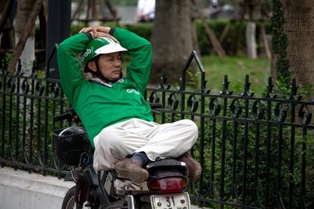 Grab motorbike taxi driver taking a break in Vietnam