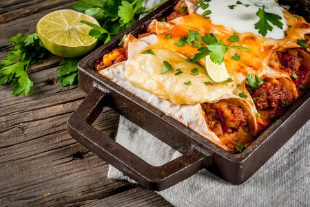 Traditional dish of spicy beef enchiladas with corn, beans, tomato