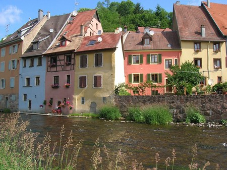 Houses line a river in Alsace