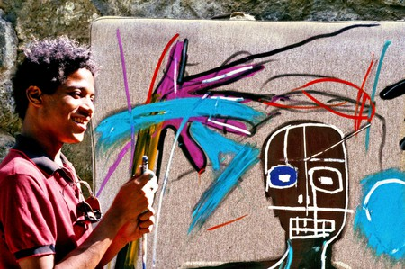 Jean-Michel Basquiat in front of his painting