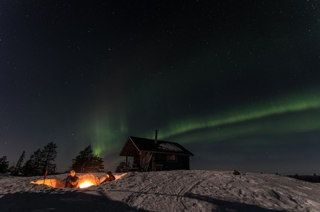 A campfire under the Northern Lights in Finnish Lapland