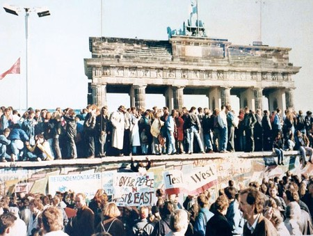 West and East Germans witnessing the fall of the Berlin Wall at the Brandenburg Gate, 1989