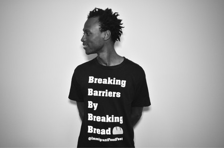 "Immigrant Food Fest Co-Founder Daniel Bright shows off the festival's motto: ""Breaking Barriers by Breaking Bread"""