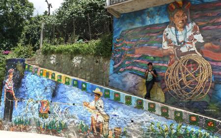 Miguel Ujpán in front of his mural in San Pablo la Laguna, Guatemala  