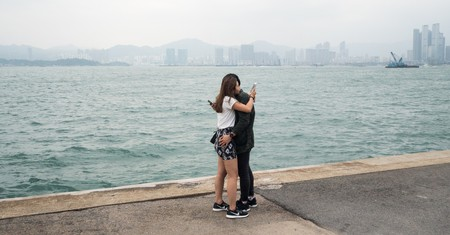 """A couple is sharing an embrace while checking their phones at the """"Instagram Pier"""", Hong Kong"""
