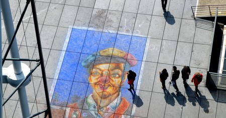 A group of people admire a piece of street art in front of the Centre Pompidou in Paris