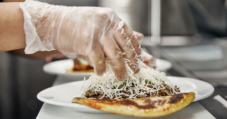 A chef sprinkles cheese on an arepa