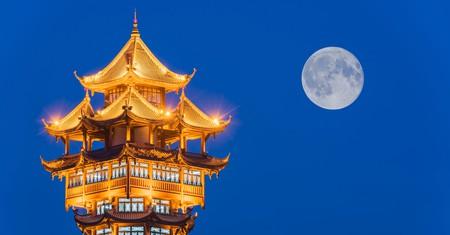 Chengdu's Jiutian tower stands illuminated under the original, natural moon