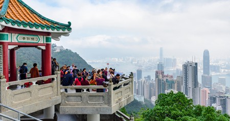Crowds of people look over the skyline of Hong Kong at the Lions Pavilion at The Peak