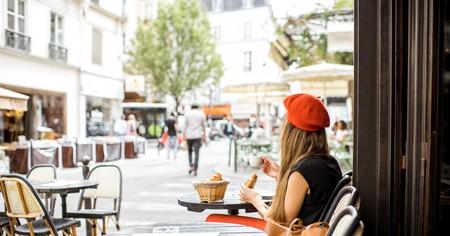 A woman enjoys a French breakfast at a café