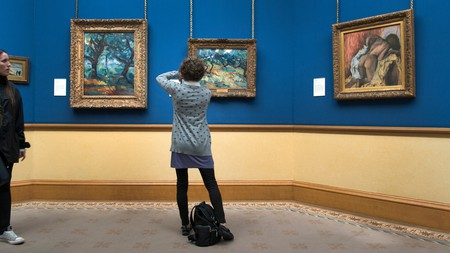 A visitor photographs Vincent Van Gogh's 'Olive Trees' (1889) at the National Gallery of Scotland