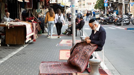 A carpet seller repairing a rug on the street in front of his shop in Old Jaffa, Tel Aviv