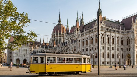A classic tram rides past the Hungarian Parliament building in Budapest
