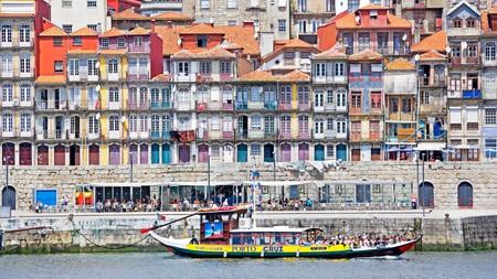 A boat passes alongside Porto riverfront