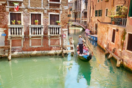 Tourists explore the canals of Venice by gondola