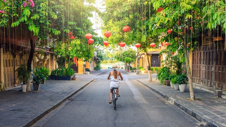A solo woman traveler visits the old city of Hoi An in Vietnam by bike