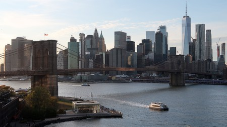 An NYC East River ferry sails in front of the Brooklyn Bridge