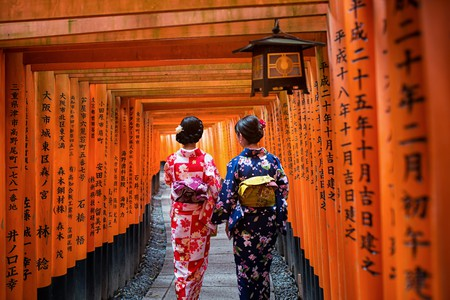 Two geishas wearing traditional japanese kimono among red wooden Tori Gate at Fushimi Inari Shrine in Kyoto, Japan. Fushimi Inari Shrine one of famous landmarks.