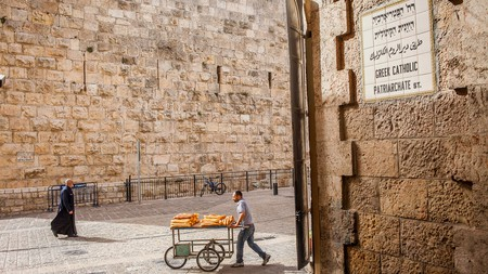 A bread vendor walks down Greek Catholic Patriarchate Street, near Jaffa Gate in the Old City, Jerusalem