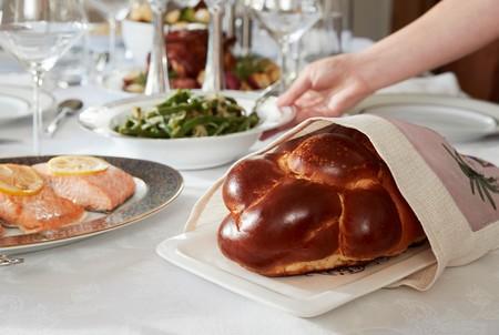 Hand placing dish on table set for Jewish Shabbat, close up