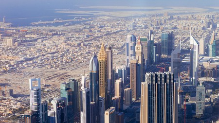 Dubai's spectacular skyline from above shows the contrast of the old desert city in the distance and the high-rise modernity of today