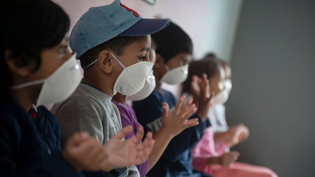 Children wear masks as they sanitise their hands at a preschool in Lenasia, Johannesburg