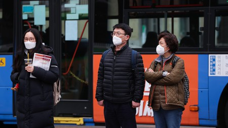 People wear masks while waiting to cross the road in Seoul, South Korea