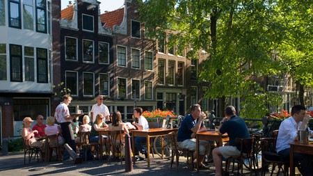 Outdoor dining on the canal bridge in Jordaan, Amsterdam. Now you can enjoy food and drink experiences like a local