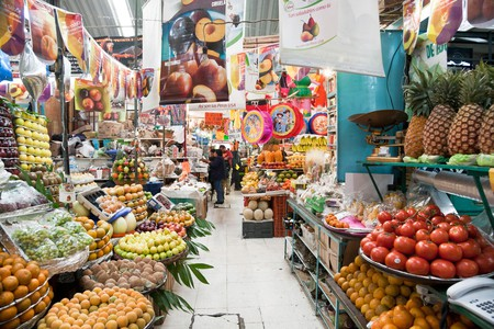distant people wandering aisle of Medellin market stacked high with staggering variety of temptingly arranged fresh fruit Roma district Mexico City