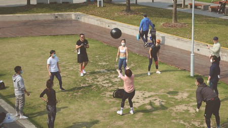 Young people take part in an outdoor fitness class, but they continue to wear masks and keep their distance from each other