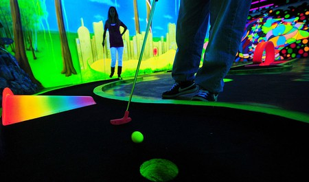 A couple play minigolf in a blacklight m