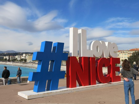 Tourists hang out and pose for selfies by the # I Love Nice slogan