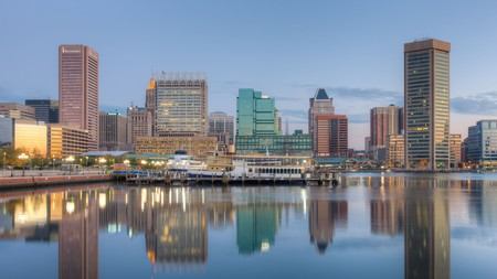 Baltimore skyline at dawn, including the Transamerica Tower and World Trade Center, reflected in the waters of the Inner Harbor